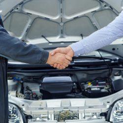 Car mechanic and customer shaking hands.